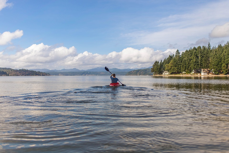 Person kayaking in beautiful blue lake: unique travel destinations.
