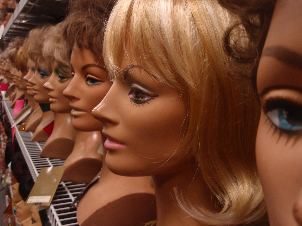 Row of female head mannequins with different colour and style of wigs.
