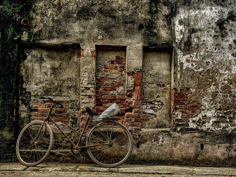 Old bicycle leaning against ruined wall in Hanoi.