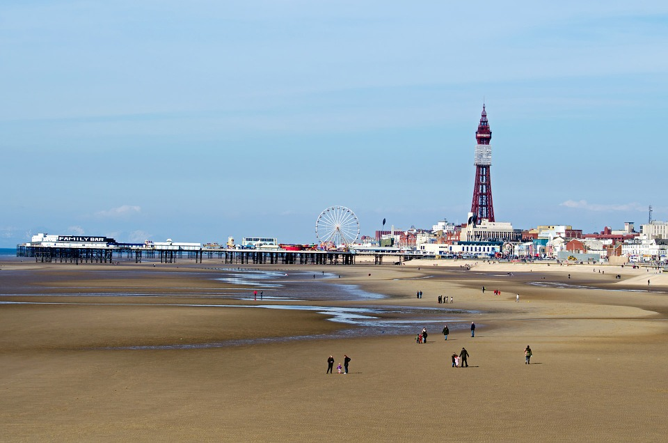 People walking on the beach in low tide with a view of a pier and tower in the distance
