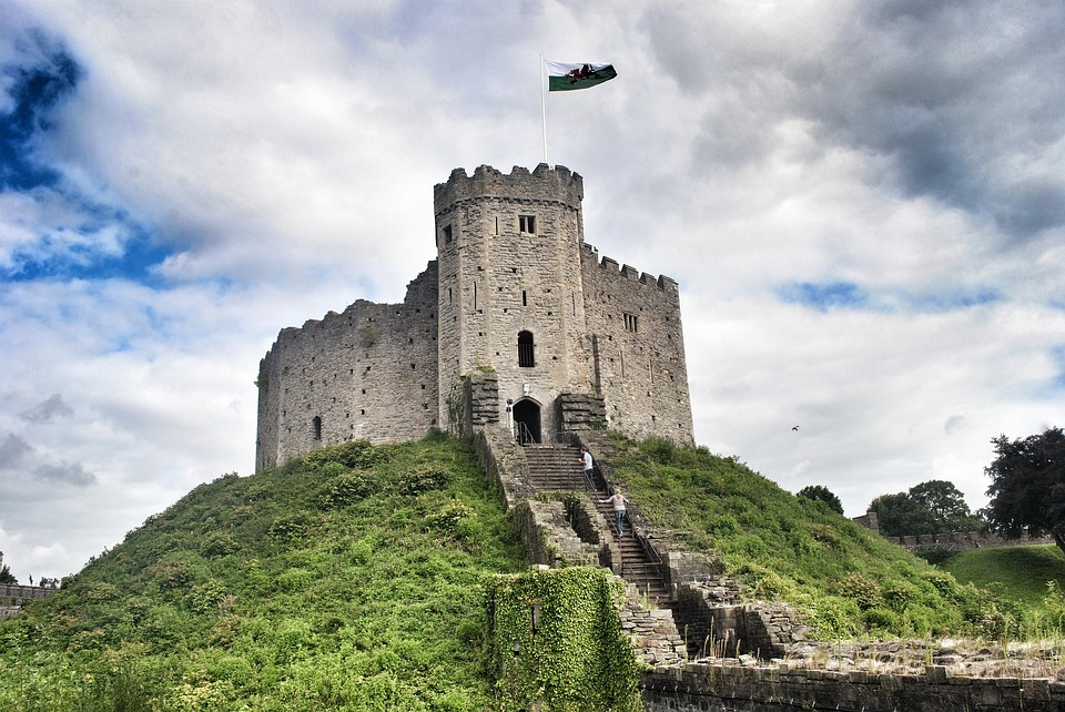 two people walking up steps to get to a small castle on a mound: summer UK day trip