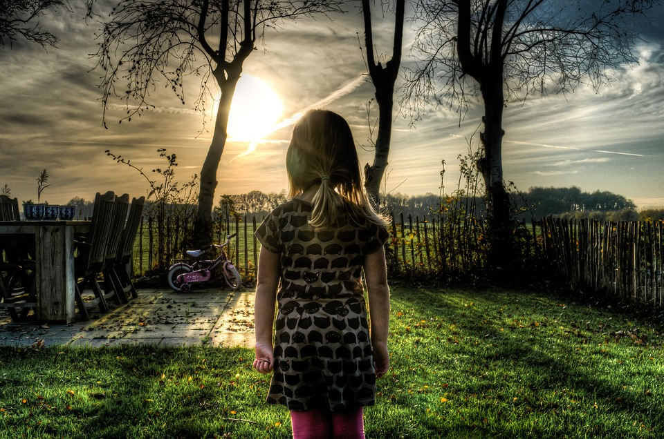 Blond young girl looking out on house garden with sunset in front of her.
