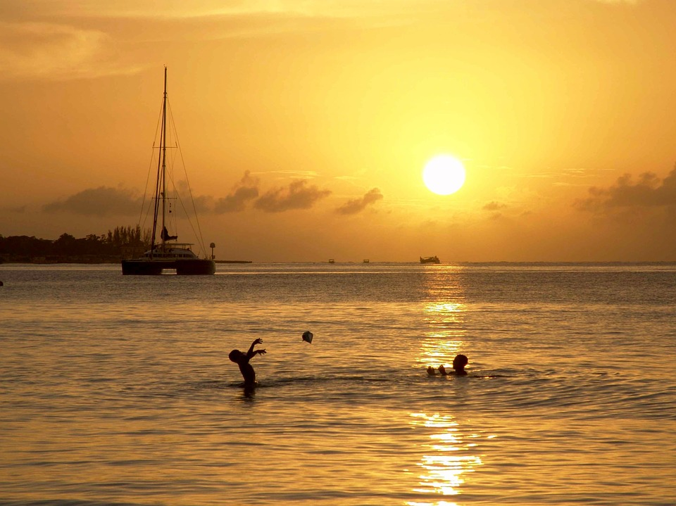 exotic honeymoon: children swimming in sea in sunset.