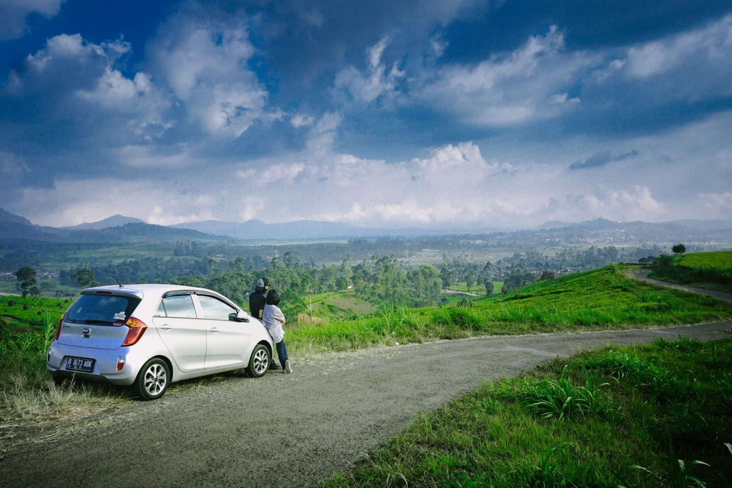 safe road trip: couple outside their car looking green valley.