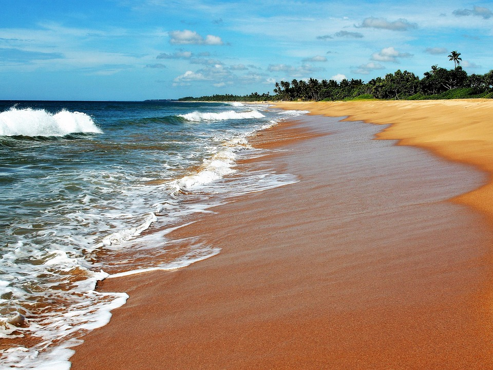 exotic honeymoon: waves hitting the shore on tropical beach.