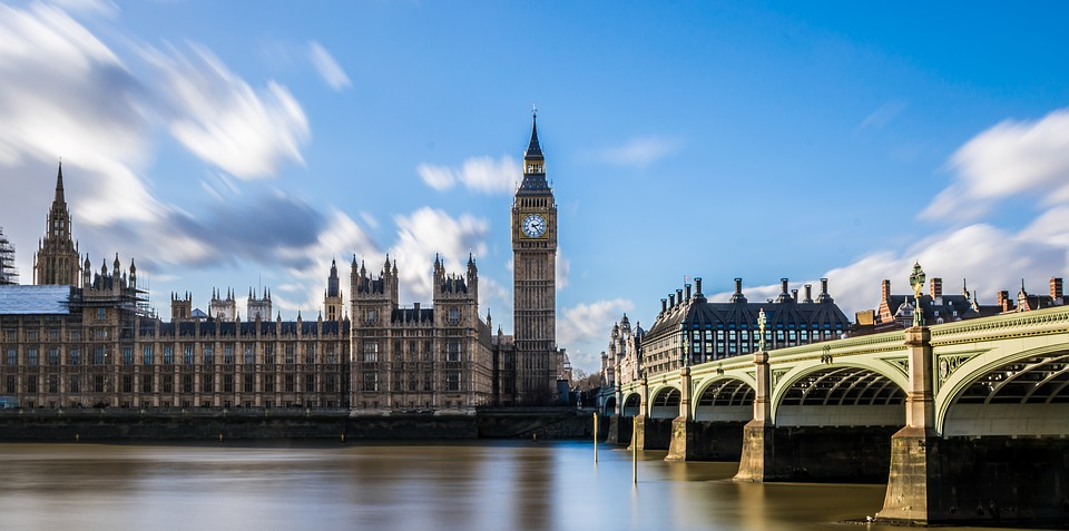View of the Houses of Parliament in London over the Thames River with a bridge to the right hand side