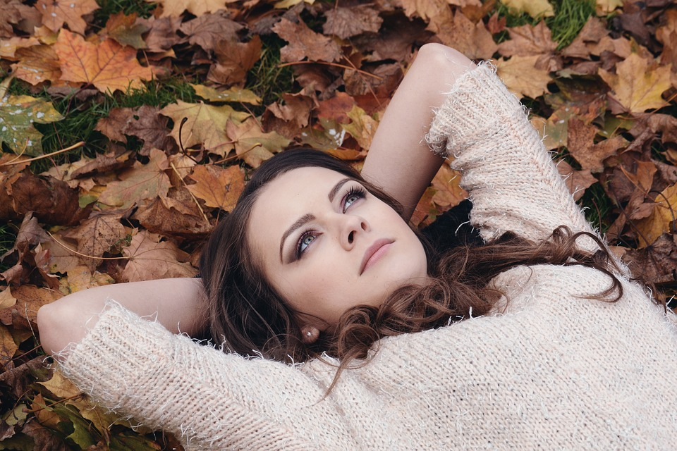 Mental health: Young lady in sweater lying on autumn leaves with hands behind her head and looking up.
