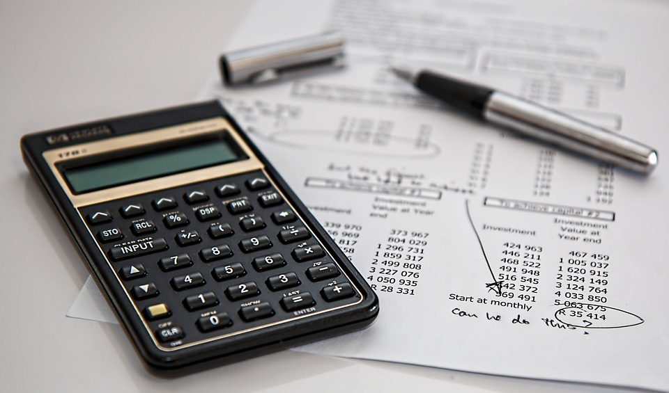 financially savvy: bills, black calculator and ballpoint pen on a desk.