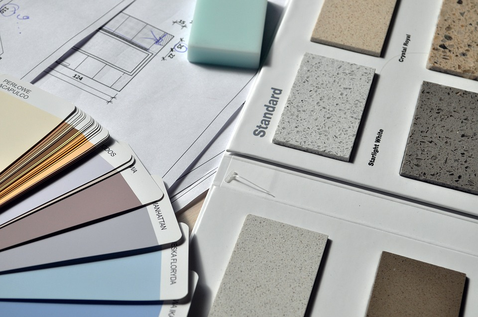 Paint colour samples assorted on desk with house plans.