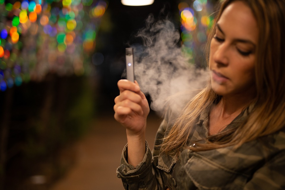 electronic cigarettes: young woman puffing on one.