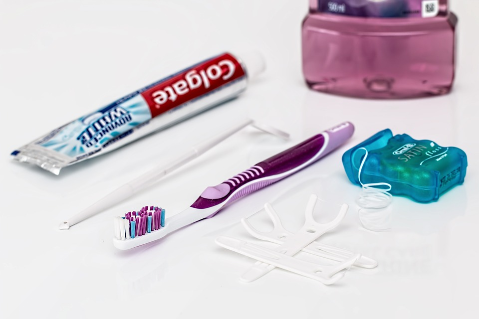 preventative dental care: toothpaste, toothbrush, dental floss on white table