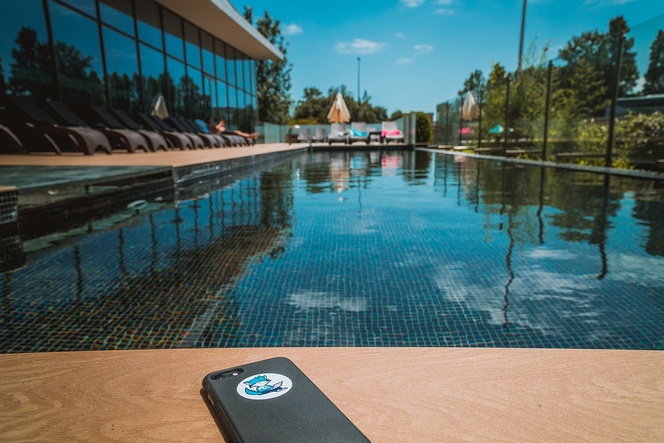 digital detox: Gorgeous sunny blue open air pool with a table at front of shot with a mobile phone on it.