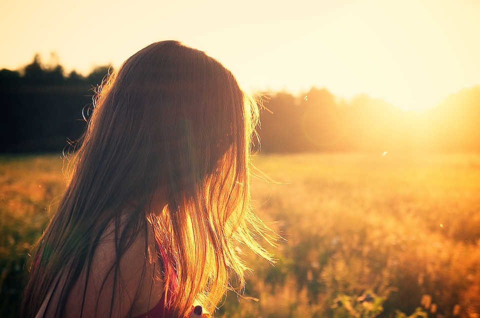 feel good about yourself: Young lady looking at setting sun in green field