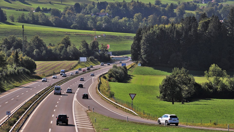 Motorway dual carriageway on a sunny day, green grass and trees on either side.