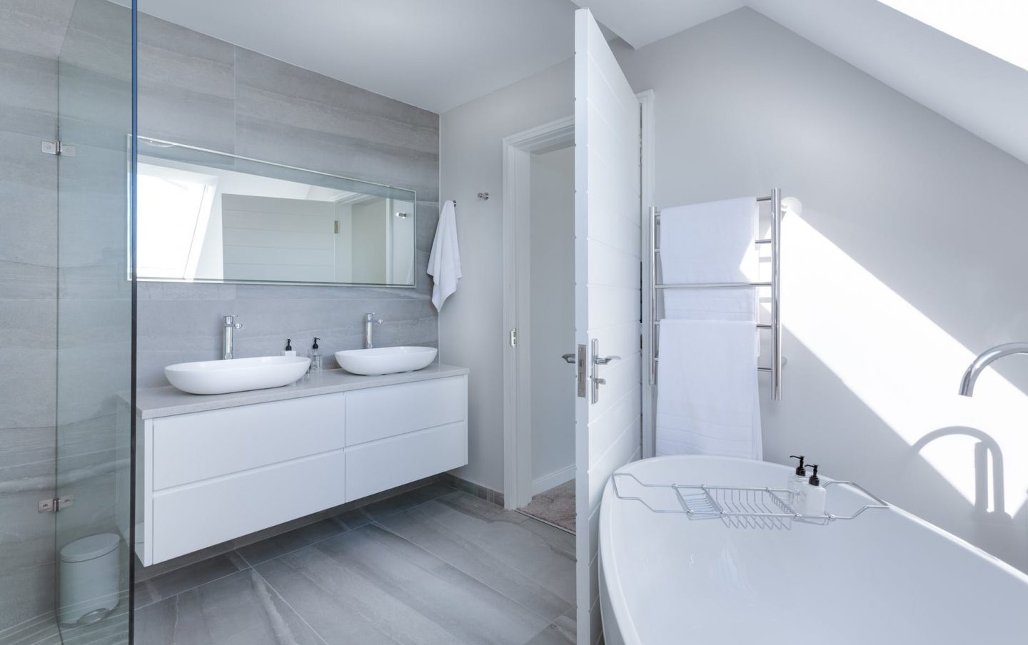 White colour themed bathroom with large sink and mirror and bathtub.