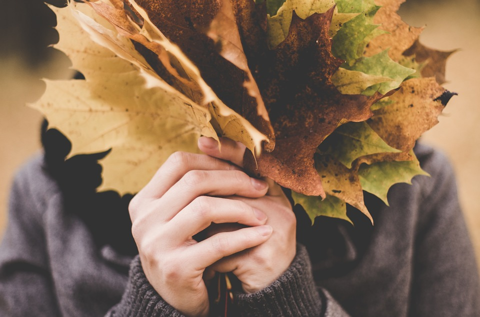 Woman holding a bunch of brown leaves up to her face.