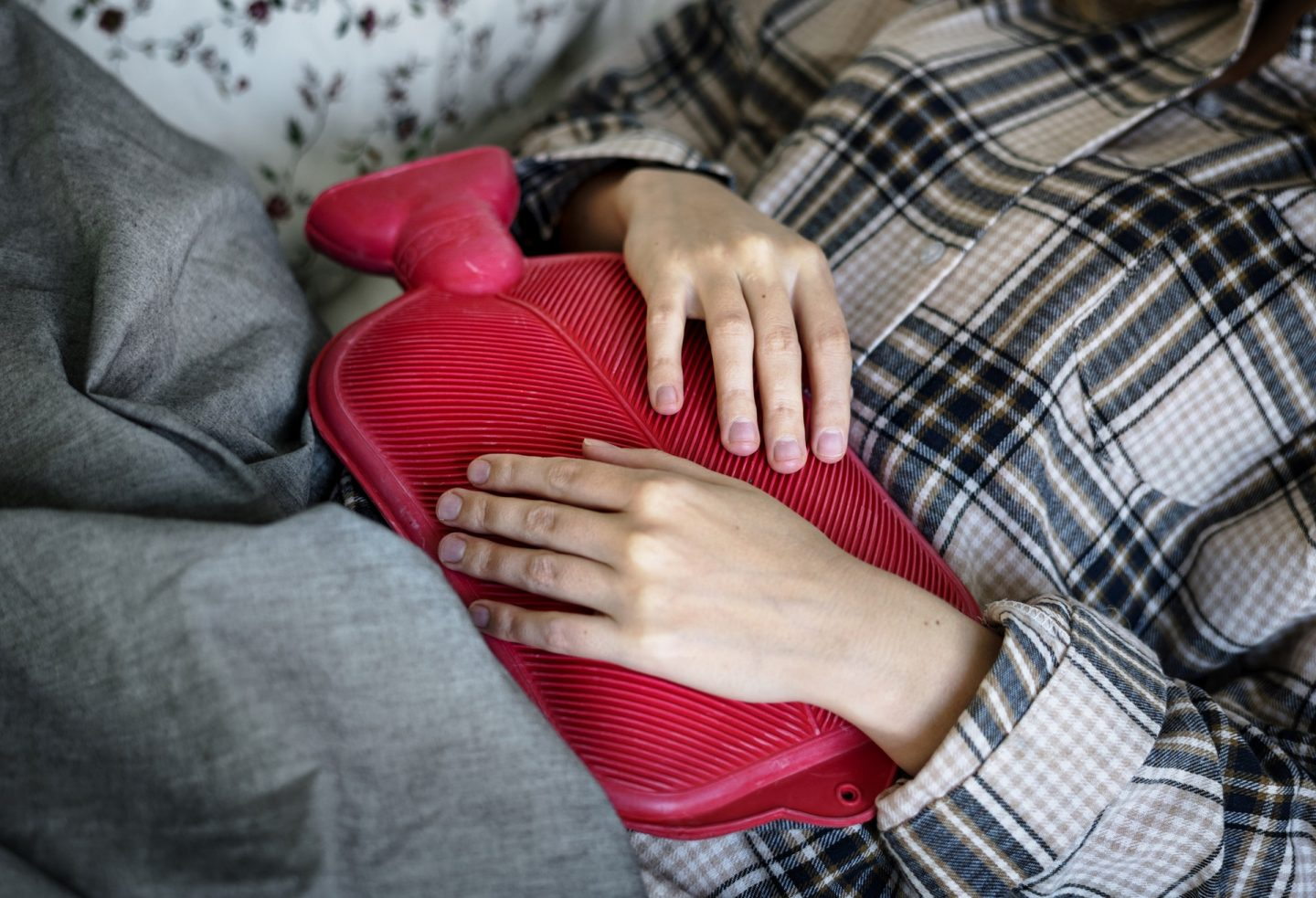 PCOS: Woman in pyjamas holding red hot water bottle on her stomach.