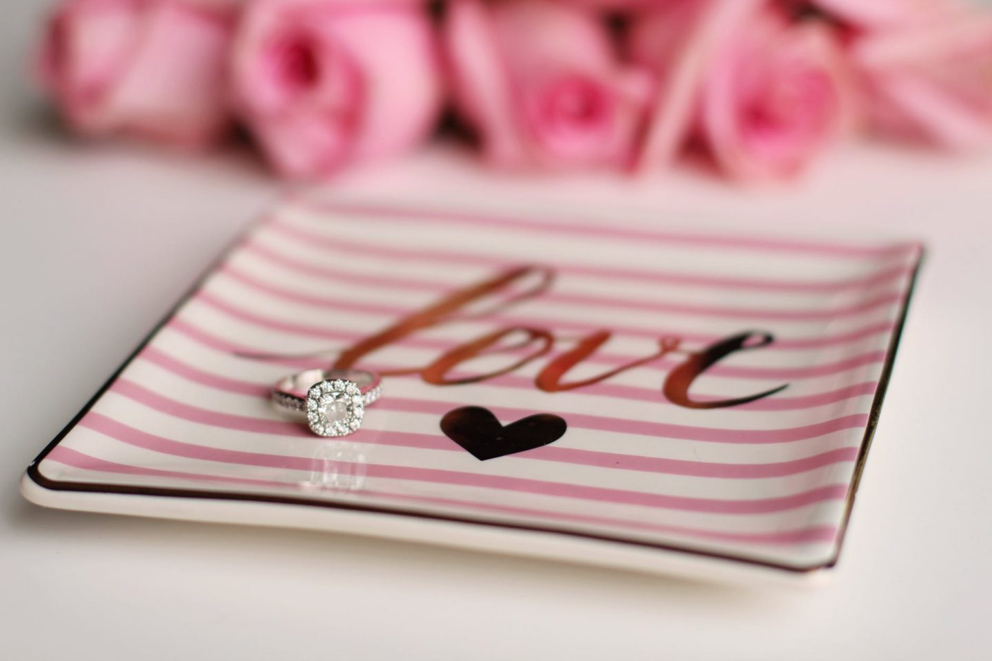 Silver diamond ring on a pink and white plate with 'love' and a picture of a heart on it.