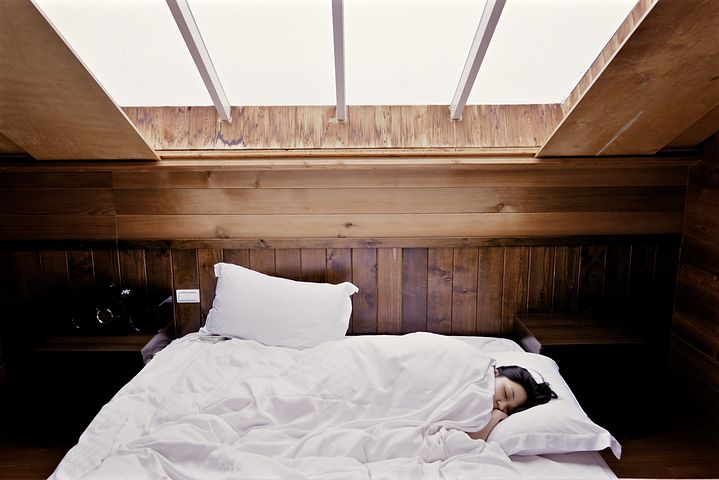 Chronic Fatigue Syndrome: Young woman in bed, covered by big white duvet under a large skylight.