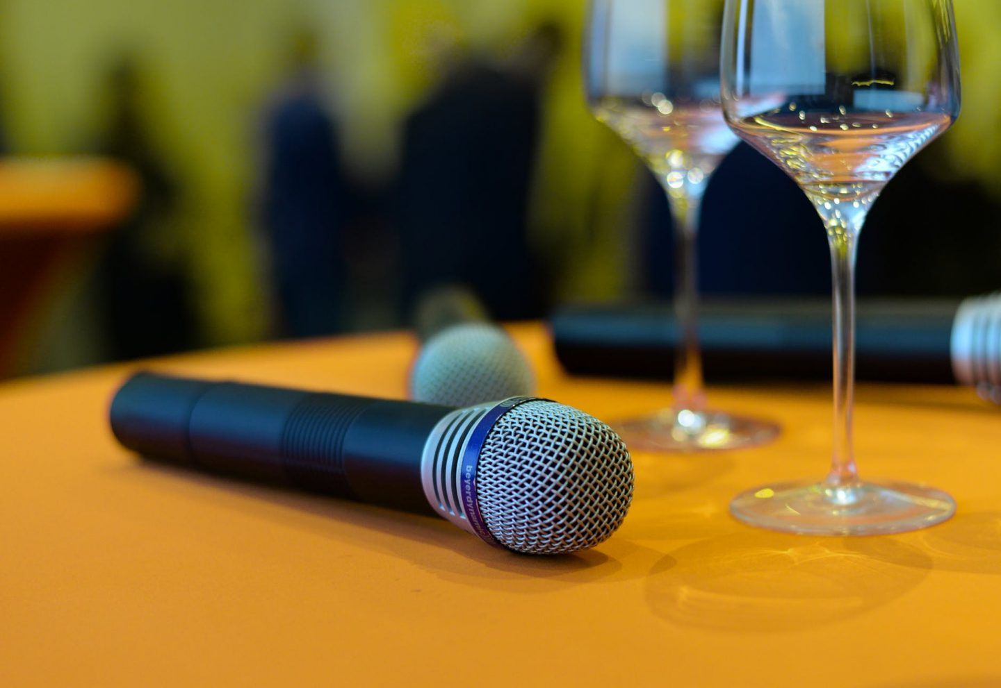 speech lessons: Black and silver microphone on beech wooden desk beside wine glasses.