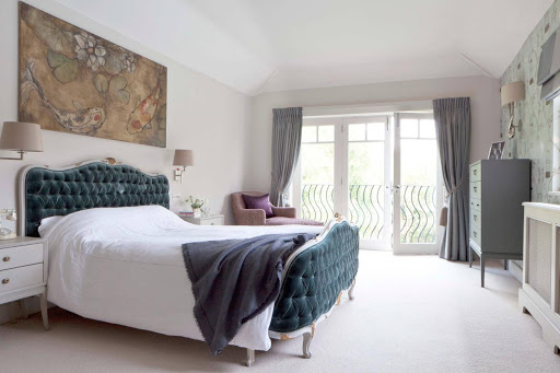 Blue velvet framed bed in large airy bedroom.