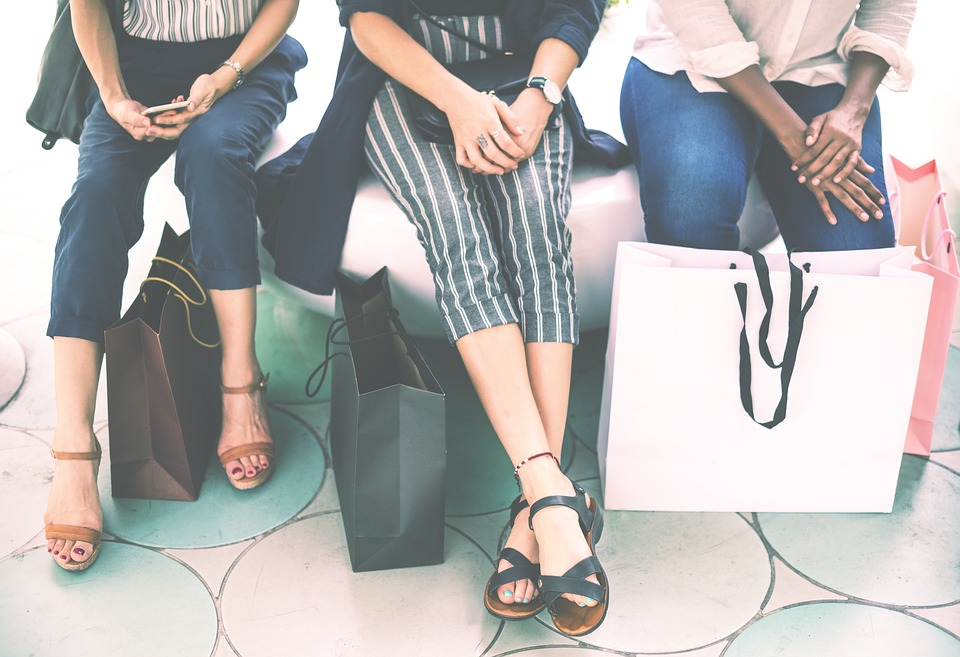 loyal to brands: women sitting on a bench surrounded by shopping bags
