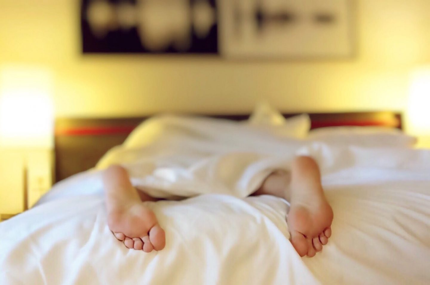 SAD: Woman in bed with bare feet dangling off end of the bed.