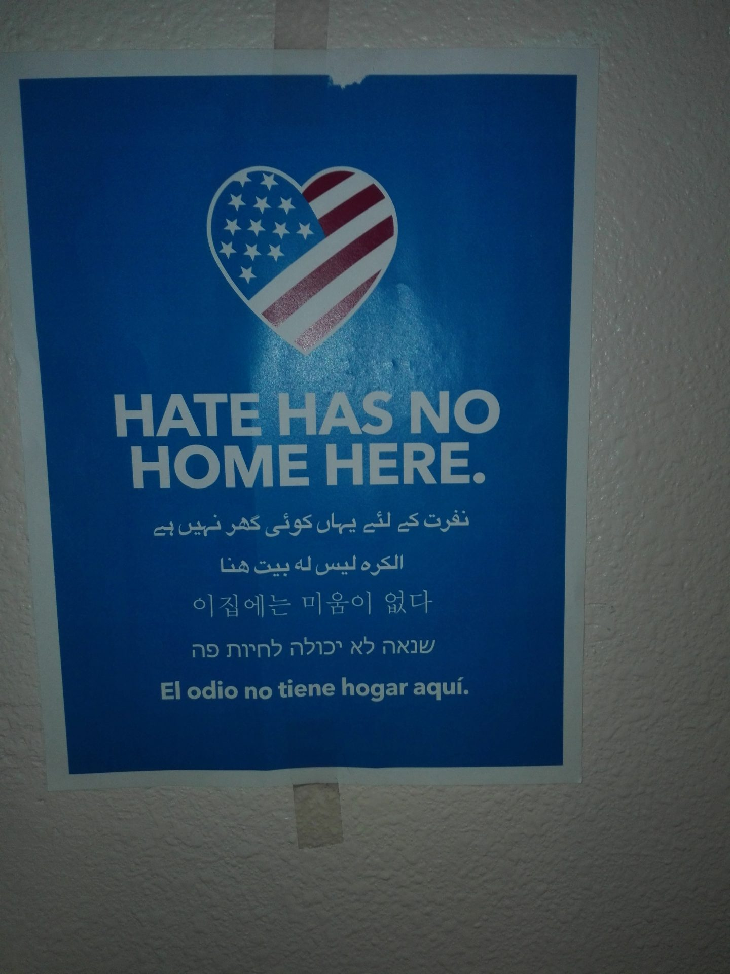 """U.S flag inside a heart shaped design and wording below saying """"Hate has no home here""""."""