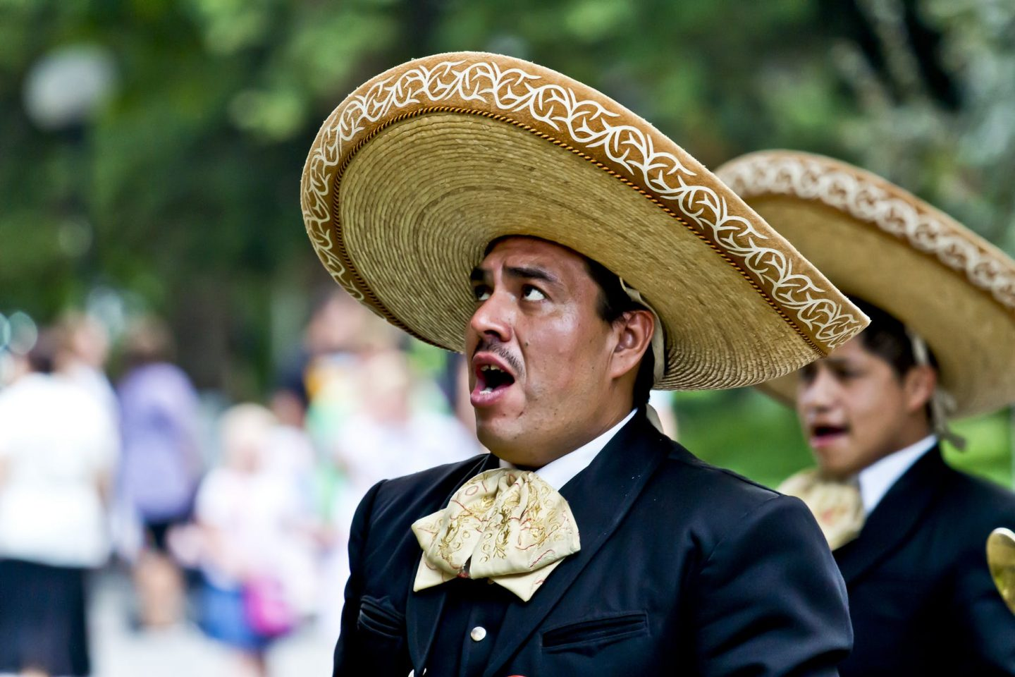 Mariachi singers with black suits and large sombreros.