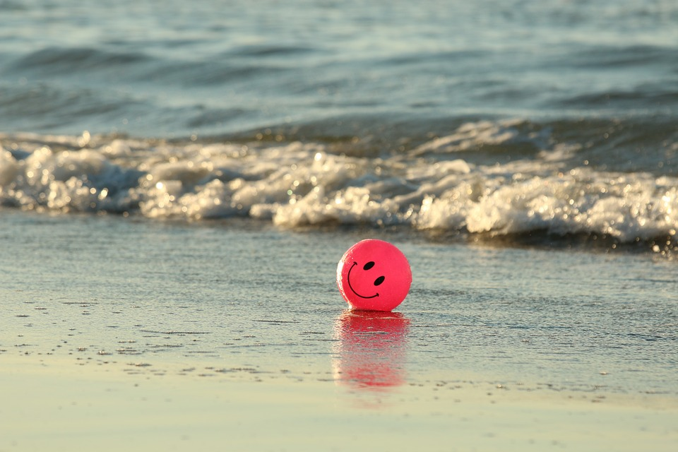 negative thinking: red small round foam piece with smiley face drawn on it on seashore.