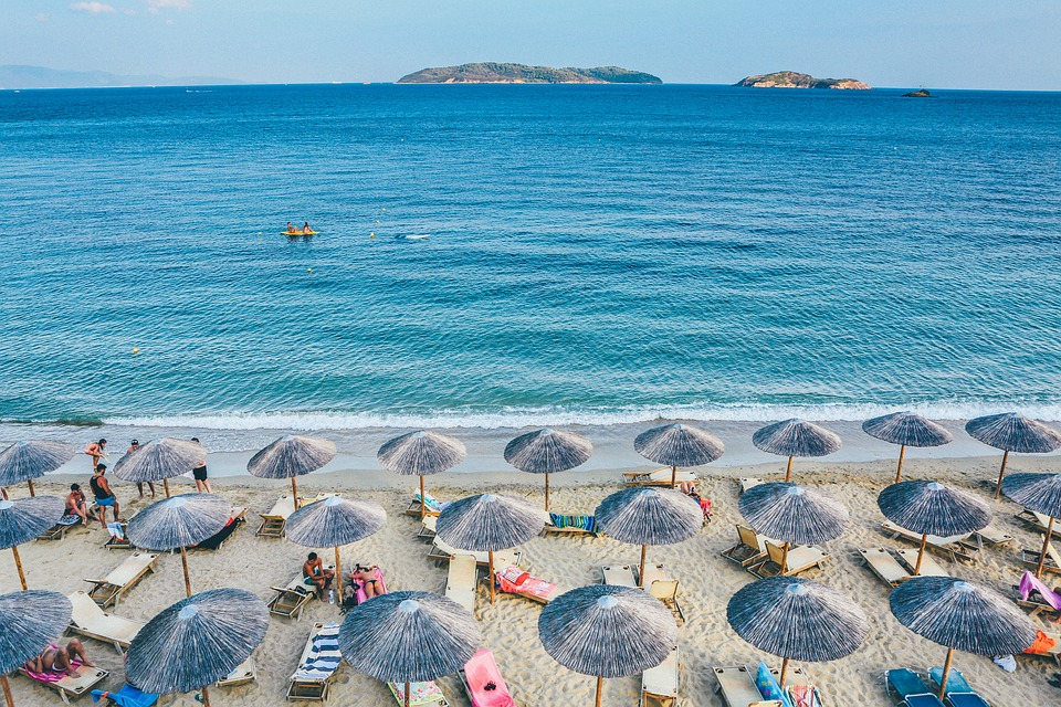 blue sea, white beach, lots of beach umbrellas in rows.