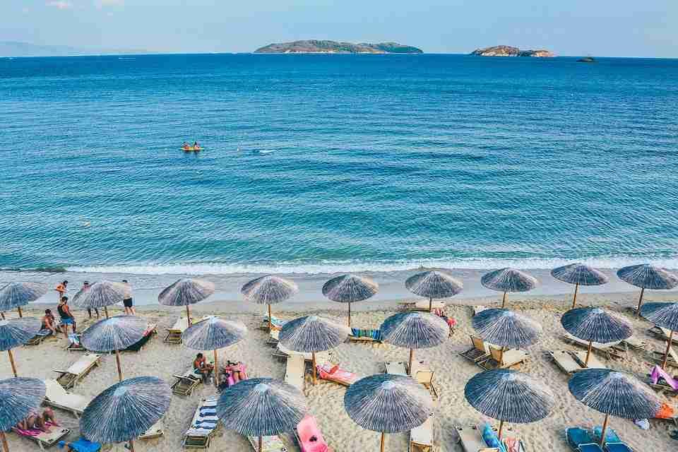 blue sea, white beach, lots of beach umbrellas in rows.
