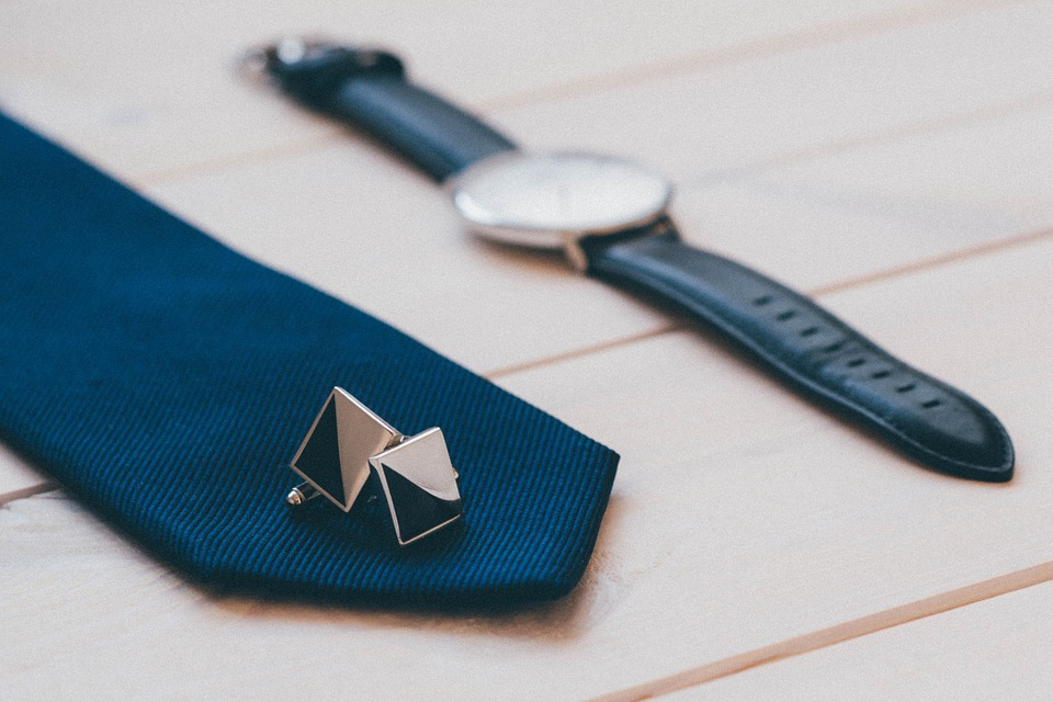 men's jewelry: blue tie, blue leather watch and silver cuff links.