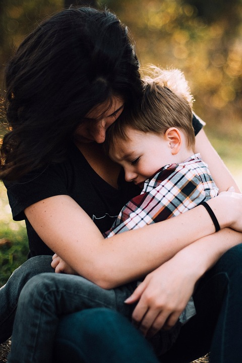 foster carer: woman holding young boy in her arms.