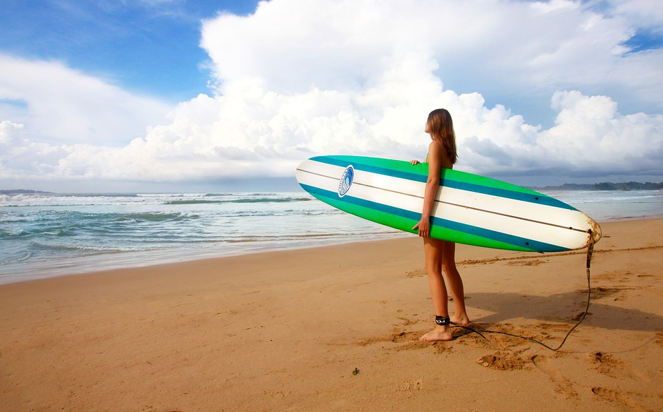 holiday resort: surfer holding board on shore looking at the sea.