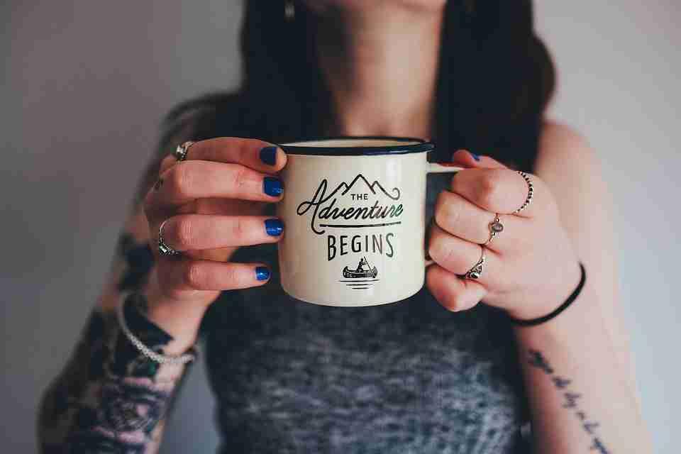 tattoo removal: tattooed woman holding mug up.