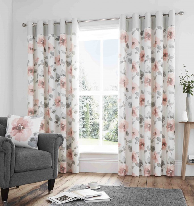 cosy bedroom: bedroom grey sofa chair with flower patterned curtains behind it adorning large window.