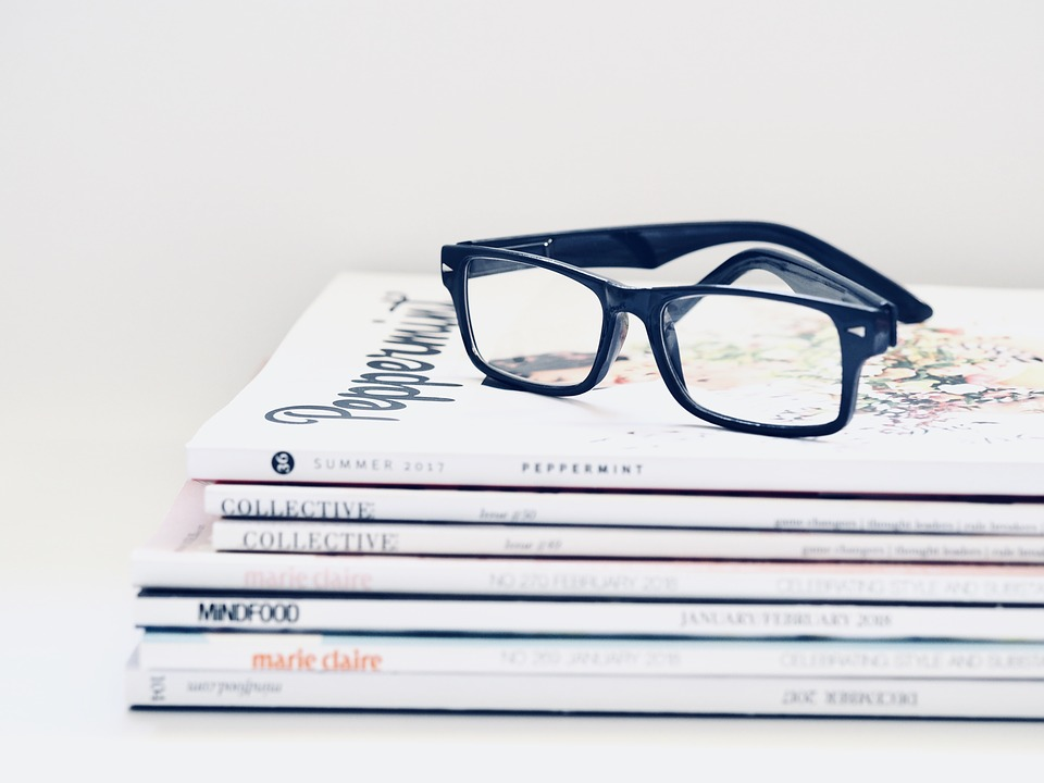 digital: blue glasses on top of pile of books.