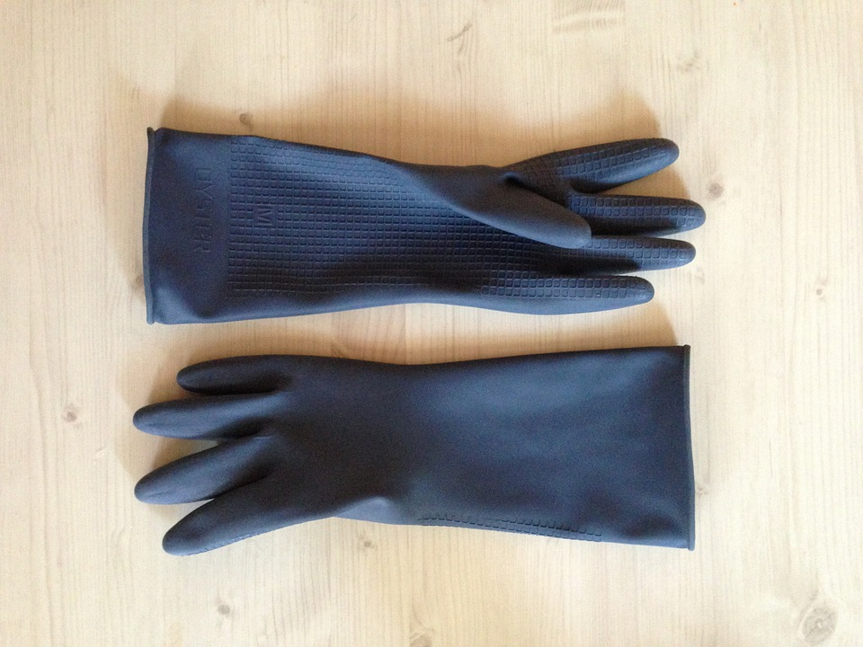 overhaul clean: blue pair of gloves on beech wood table.