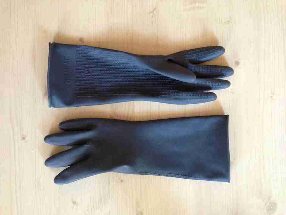 overhaul clean: blue pair of gloves on beech wood table.