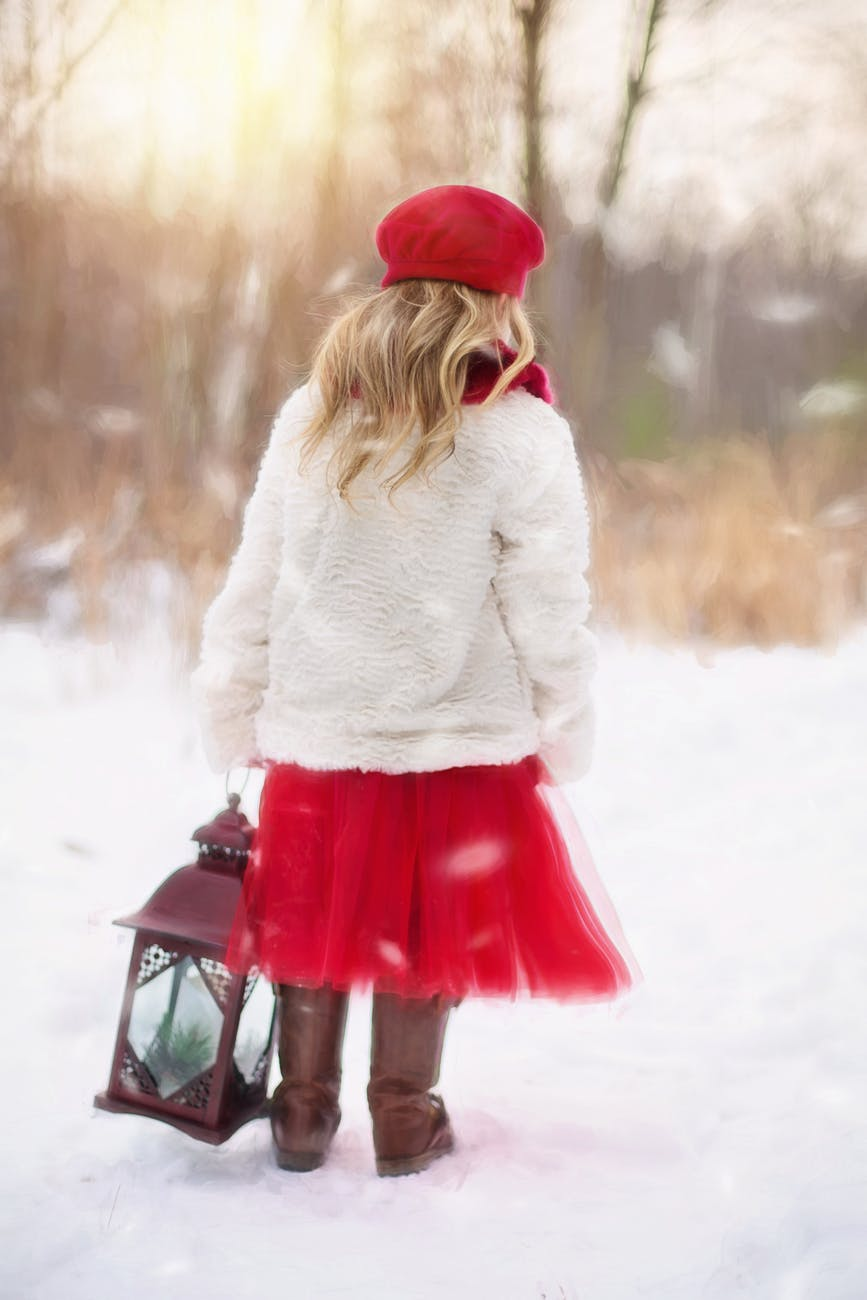 Dress Your Child: little blond haired girl walking in snow with lantern, with red hat, white jumper, red skirt and brown boots.