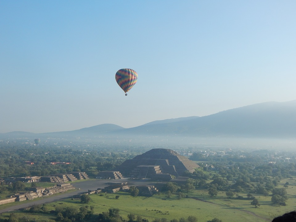 inspirational Mexican places: Pyramids in sunny distance with hot air balloon flying above them.
