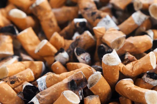 Smoking: Collection of brown cigarette buts in ashtray.