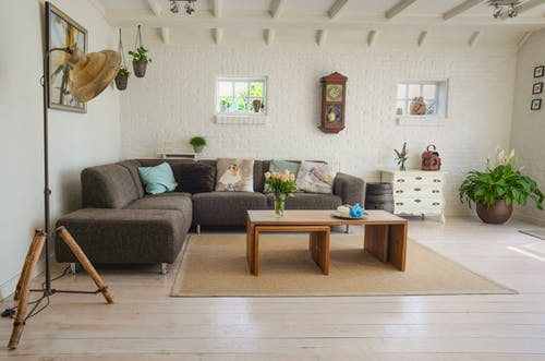 Staging your home: pristine living room with sectional lounge and wooden coffee table.