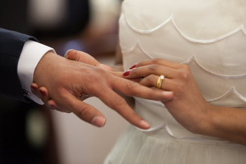 resorts wedding: bride placing wedding ring on groom's finger.