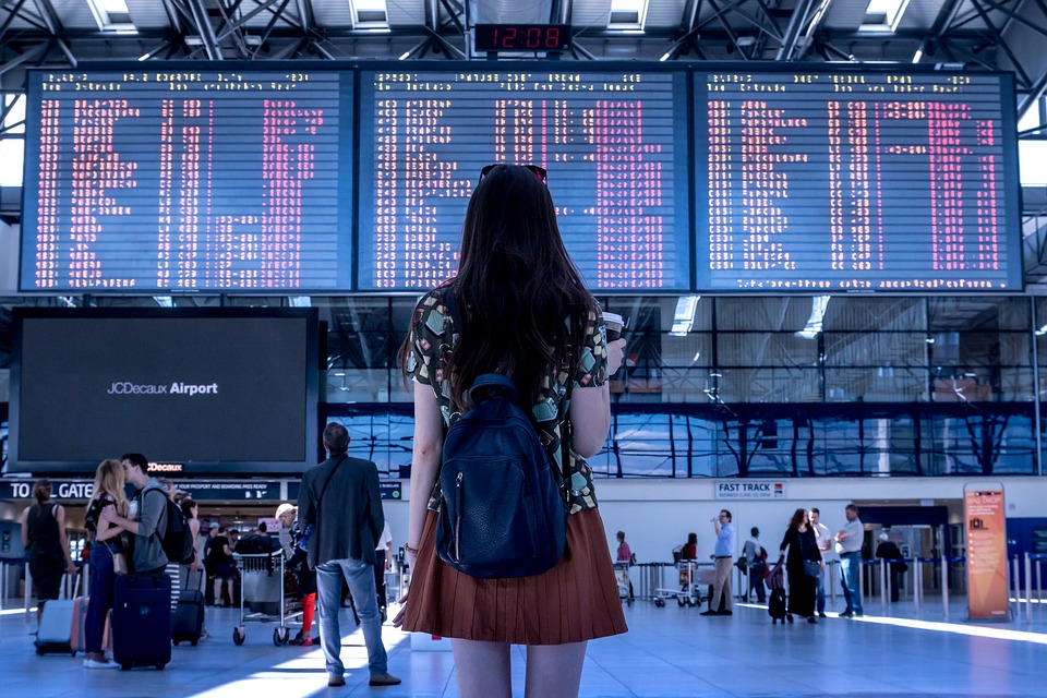 Travel differently: Young lady with rucksack looking at airport departure board