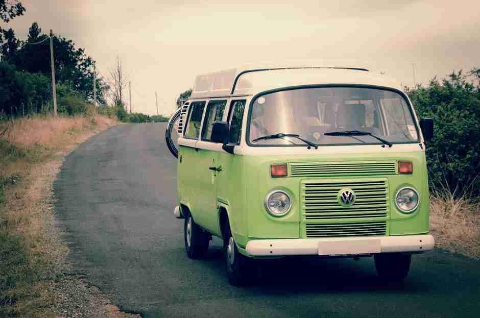 van life: bright green VW Campervan on country road.