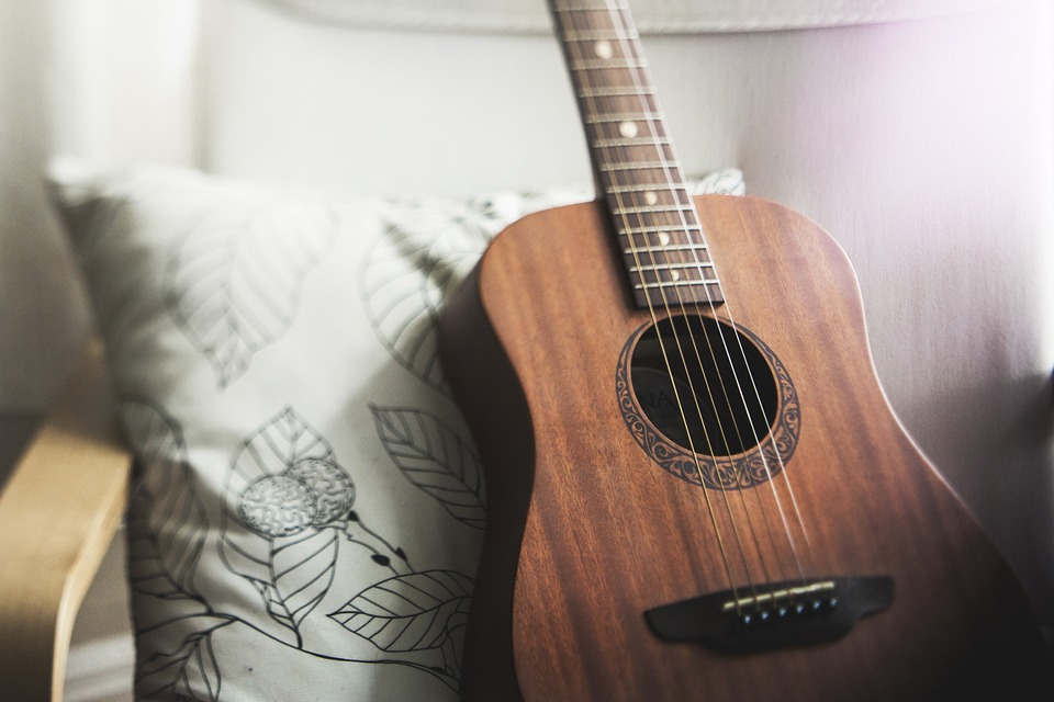 guitar sitting on chair and leaning on a cushion
