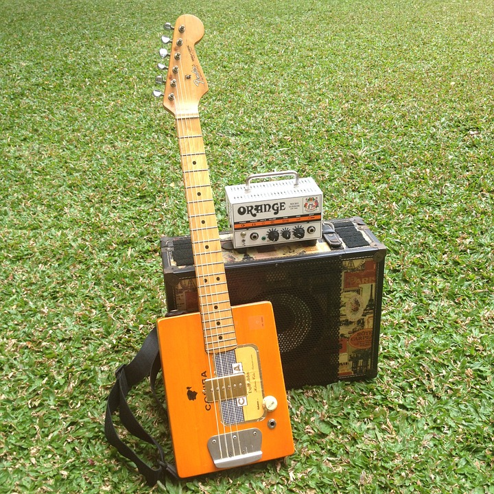 cigar box guitar leaning on an amp and both  are set on  grass