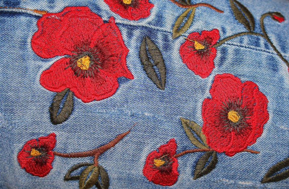 Embroidered patches: Red roses patch on blue jeans.